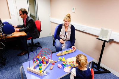 kvinde og mand udfører undersøgelse af barns hørelse i audiometrirum